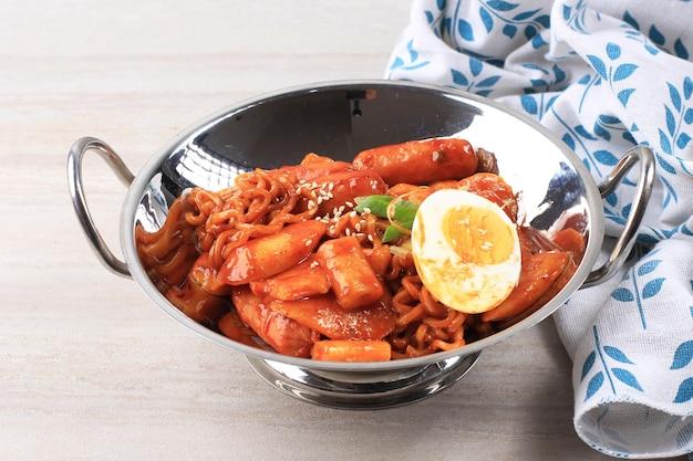 Rapokki oder rabokki, tteokbokki mit koreanischen ramen instan nudel. gekochtes ei, geschnittene frühlingszwiebeln und sesam hinzufügen