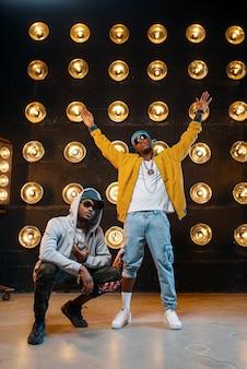 Rapper in mützen tanzen mit scheinwerfern auf der bühne