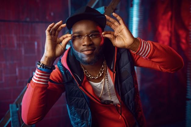 Rapper in stilvollen goldgläsern posiert im grunge-studio mit cooler underground-dekoration. hip-hop-performer, rap-sänger, breakdance-performance