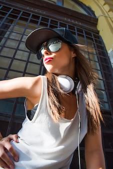 Rapper mädchen mit kopfhörern in einer europäischen stadt