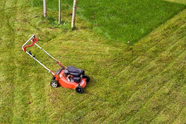 Rasenmäher, der gras auf der grünen wiese im hof schneidet