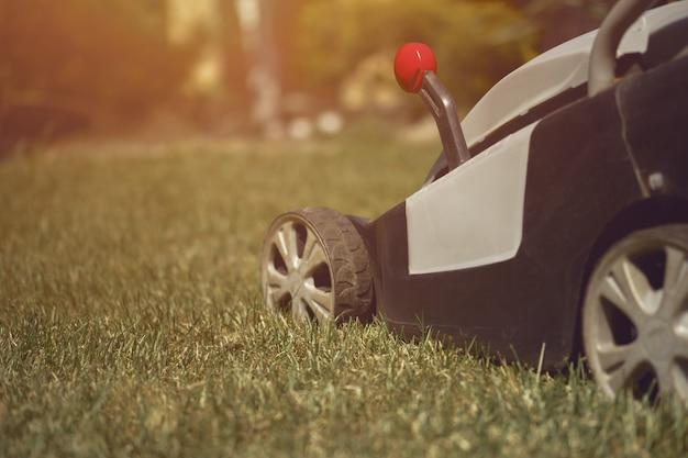 Rasenmäher, der grünes gras auf gartenpflegegeräten im hinterhof schneidet, sonniger tag, nahaufnahme