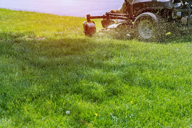 Rasenmäher, der grünes gras im garten entlang der straße schneidet