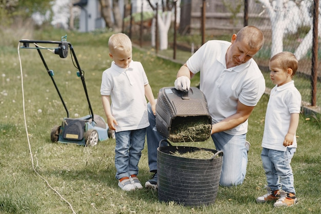 Rasenmähermann, der mit söhnen am hinterhof arbeitet