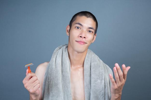 Rasieren des hübschen kerls rasiert auf dem gesicht auf grau