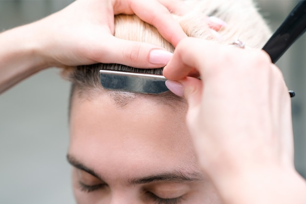 Rasiermesser. haarschnittprozess des blonden jungen mannes im friseursalon, friseurkonzept für männer und jungen