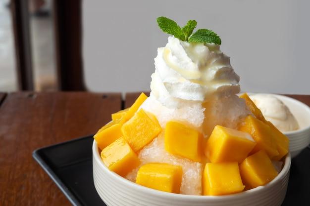 Rasierter eisnachtisch mit der mango geschnitten. serviert mit vanilleeis und schlagsahne.