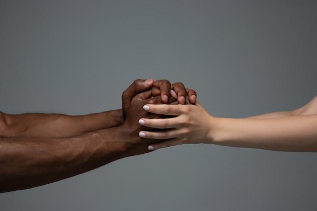 Rassentoleranz. respektiere die soziale einheit. afrikanische und kaukasische hände, die lokal auf grau gestikulieren
