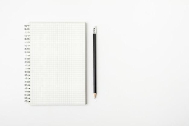 Rasterpapierbuch und -bleistift auf einem weißen schreibtisch