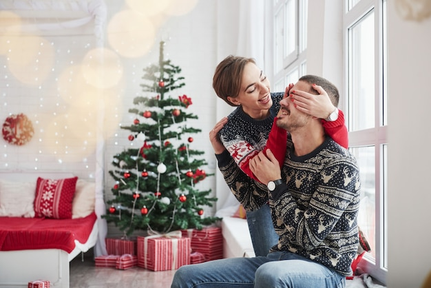 Rate mal, was ich dir schenken werde. glückliche junge leute sitzen auf der fensterbank im raum mit weihnachtsdekorationen