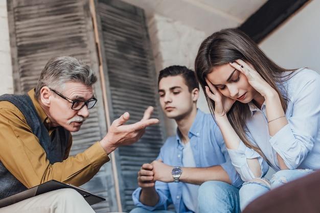 Ratschlag. nette angenehme junge paare, die ihren therapeuten betrachten und auf sie beim versuchen hören, mit ihren problemen fertig zu werden