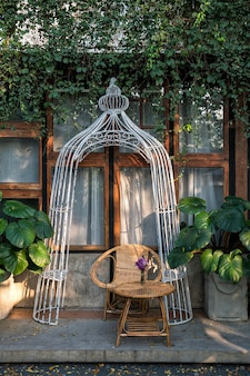Rattansitz und -tisch nahe hauptfenster mit pflanzenkletterer.