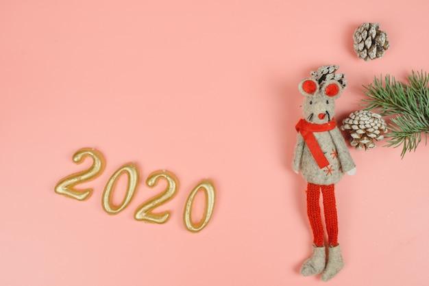Rattespielzeug als symbol von 2020 auf einem rosa pastell