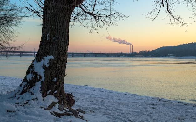 Rauch aus dem schornstein am fluss im winter