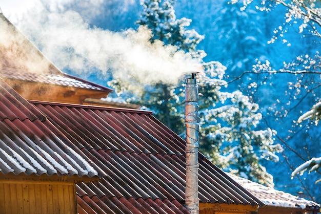 Rauch aus dem schornstein auf dem dach an einem sonnigen tag