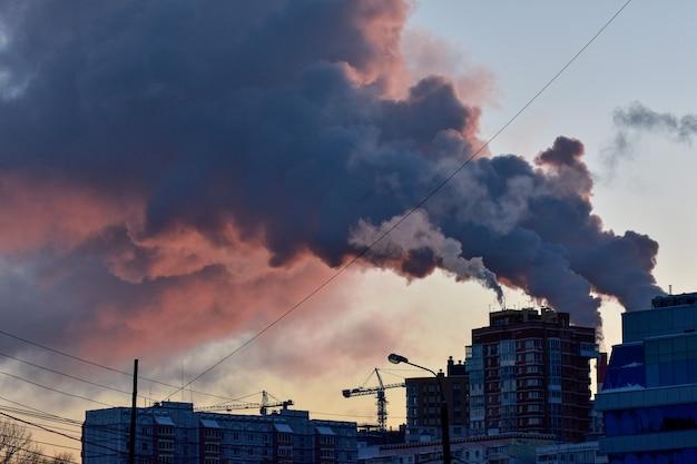 Rauch aus industrierohren bei sonnenuntergang