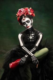 Rauch. junges mädchen wie santa muerte saint death oder sugar skull mit hellem make-up. porträt lokalisiert auf dunkelgrünem studiohintergrund mit exemplar. feiern von halloween oder tag der toten.