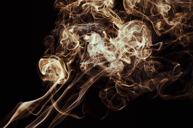 Rauch schwebt auf dunklem hintergrund in der luft