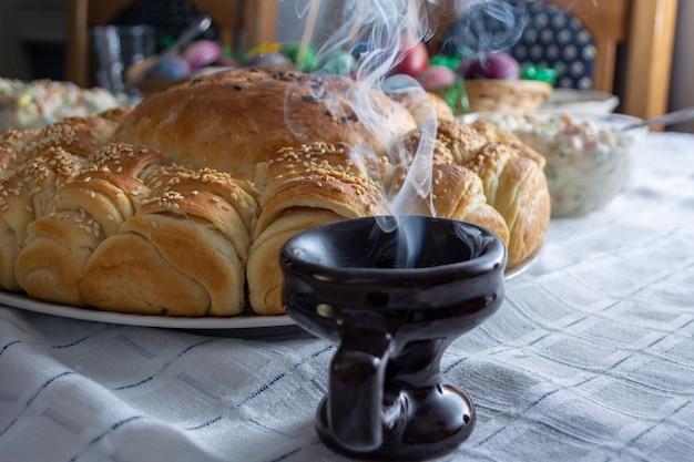 Rauch steigt von cresset auf dem tisch mit essen auf ortodoxem ostern auf