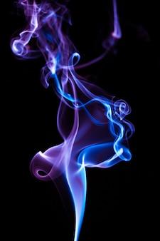 Rauchen sie auf blauer neonfarbe im schwarzen hintergrund