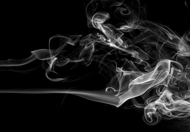Rauchen sie den weißen weihrauch auf einem schwarzen hintergrund. dunkelheitskonzept
