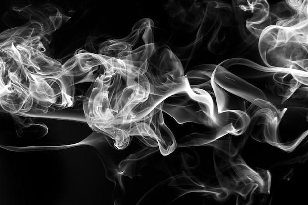 Rauchen sie den weißen weihrauch auf einem schwarzen hintergrund. feuer