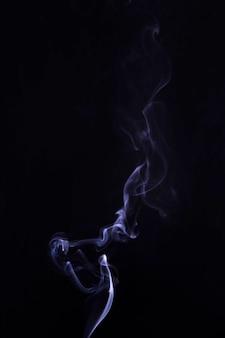 Rauchen sie in der mitte des schwarzen hintergrunds