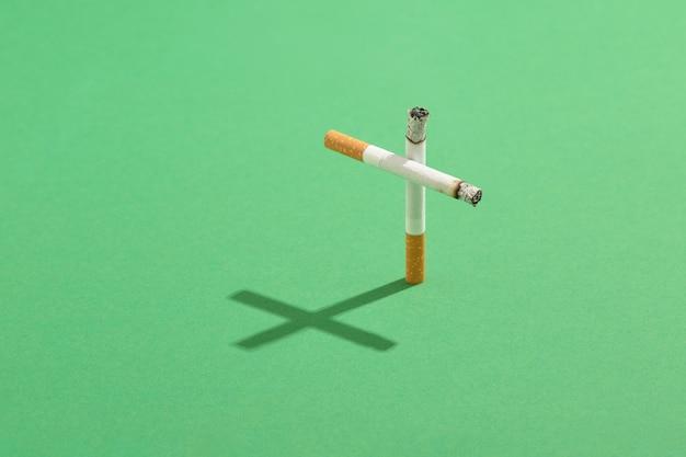 Rauchen tötet konzept mit zigaretten als grabkreuz mit dem kreuzschatten auf grünem friedhofsrasen.