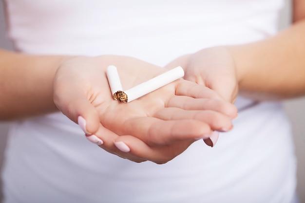 Rauchen verboten. lächelnd spaltet das mädchen eine zigarette. rauchen sie nicht bei problemen, die von nikotin abhängen.