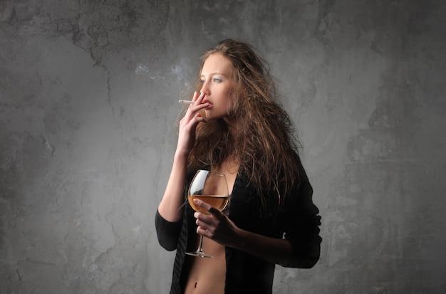 Rauchende frau trinkt wein