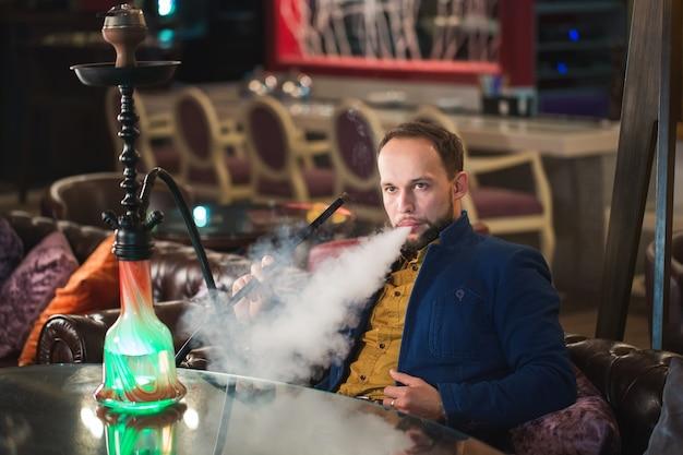 Rauchende huka, mann weht rauch