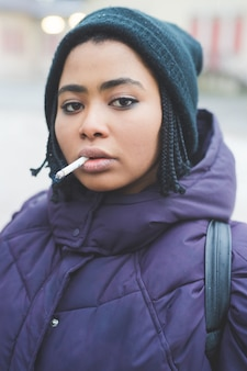 Rauchende zigarette der jungen frau des porträts