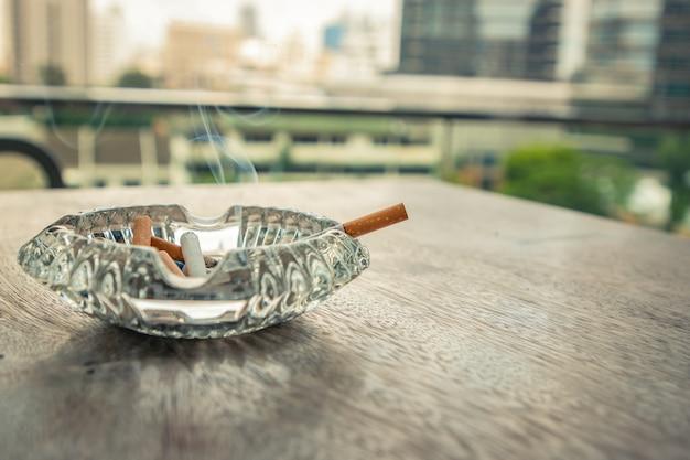 Rauchende zigarette im aschenbecher auf der hölzernen tabelle