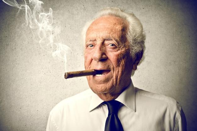 Rauchende zigarre des alten mannes