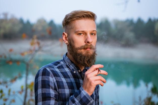 Rauchender bärtiger mann im freien in der nähe des sees am abend schlechte angewohnheitssucht nach zigaretten kaukasischer gu...