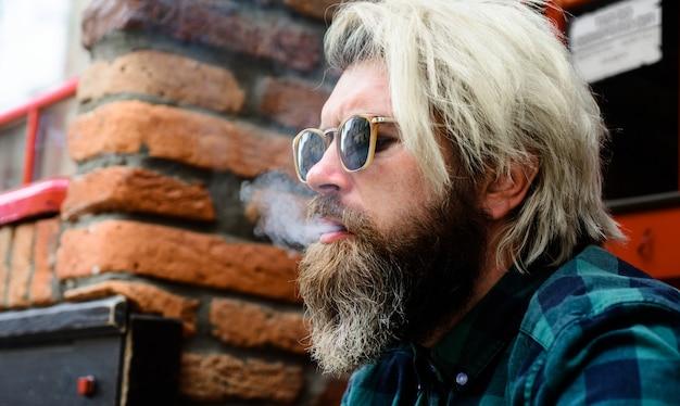 Rauchender mann. bärtiger mann raucht zigarette. nahaufnahmeporträt. gut aussehender mann, der draußen raucht. Premium Fotos
