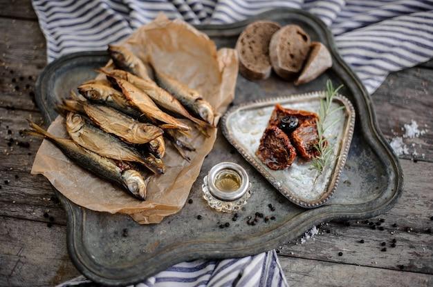 Rauchgetrockneter stöckerfisch auf dem papier auf dem metalltablett mit sonnengetrockneten tomaten, öl und brot auf der grau gestreiften serviette auf dem holztisch.