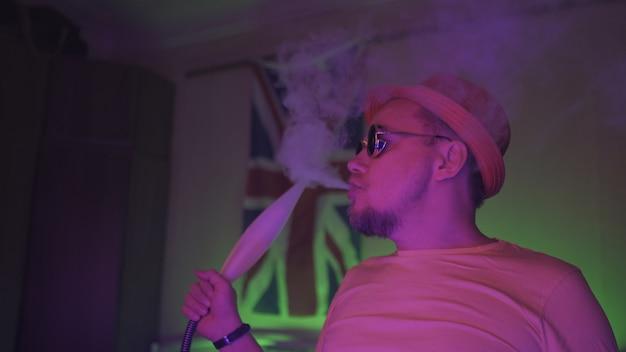 Raucht nachts eine wasserpfeife mit neonlichtern.