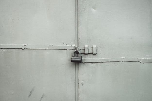 Raues metalltor auf schlossnahaufnahme. grunge hintergrund der metalltür mit vorhängeschloss. verschlossenes tor mit kopierraum. graue textur der schmutzigen industriellen wand mit verschlossenem eingang. privateigentum geschützt.