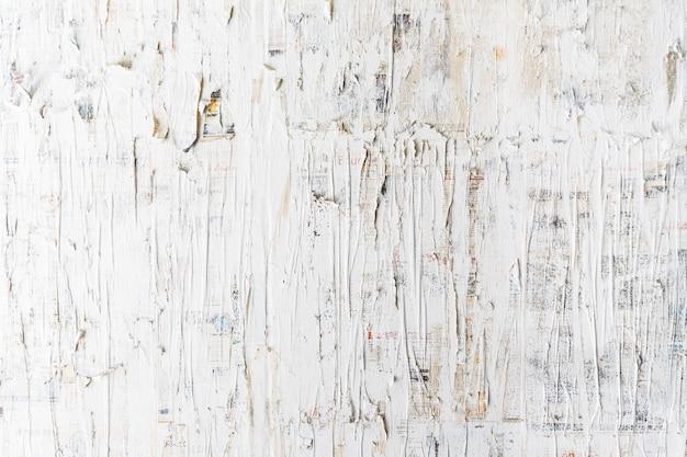 Raues weiß gemalt auf zeitungswand. perfekt für den hintergrund. abstrakte textur. weiße tapete.