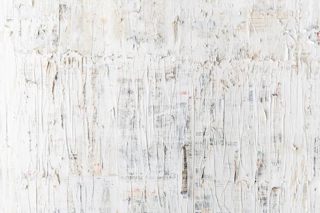 Raues weiß gemalt auf zeitungswand. perfekt für den hintergrund. abstrakte textur.
