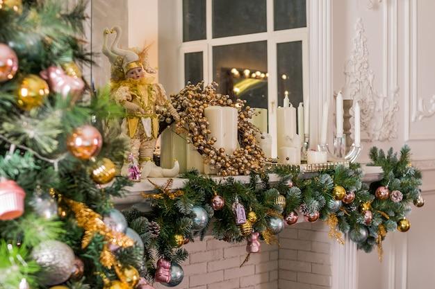 Raum beleuchtet mit girlandenlichtern verziert bereit, weihnachten zu feiern. innenarchitektur des weihnachtsraumes, weihnachtsbaum verziert durch lichter, kerzen und girlande, die zuhause kamin beleuchtet.