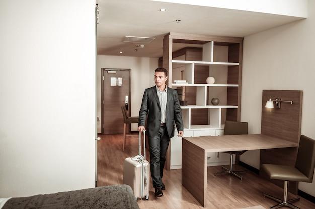 Raum betreten. junger geschäftsmann, der dunklen anzug trägt, der hotelzimmer mit seinem gepäck betritt