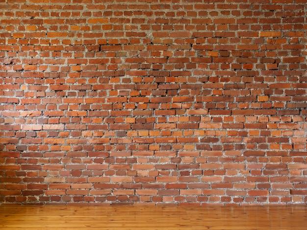 Raum mit wänden des roten backsteins und hölzernem bodenbelag von brettern