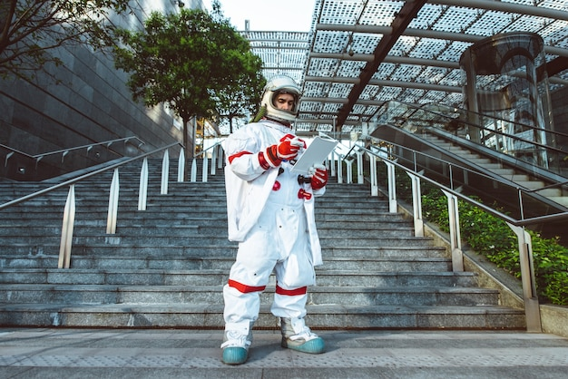 Raumfahrer in einer futuristischen station. mann mit raumanzug, der in einem stadtgebiet spaziert