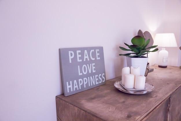Rauminnenraum der skandinavischen art des hippies. stimmungsbrett. altes zerkratztes brett, zitat frieden, liebe, glück. weiße kerzen, topf mit sukkulenten. wohnzimmer im minimalistischen stil.