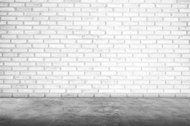 Rauminnenraum mit weißer backsteinmauer und betonboden für hintergrund, leerem betonboden und betonwand für hintergrundmontageentwurf