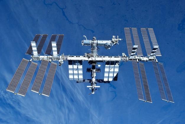 Raumstation auf dem hintergrund der erde. in erweiterter form. elemente dieses bildes wurden von der nasa bereitgestellt. für jeden zweck.