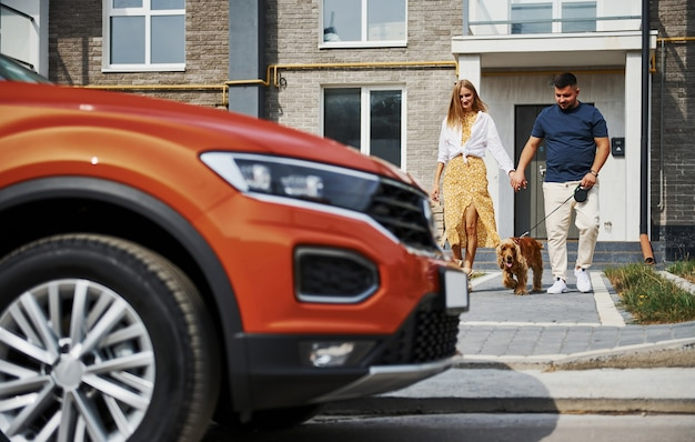 Raus aus dem gebäude. schönes paar geht zusammen mit hund draußen in der nähe des autos spazieren.