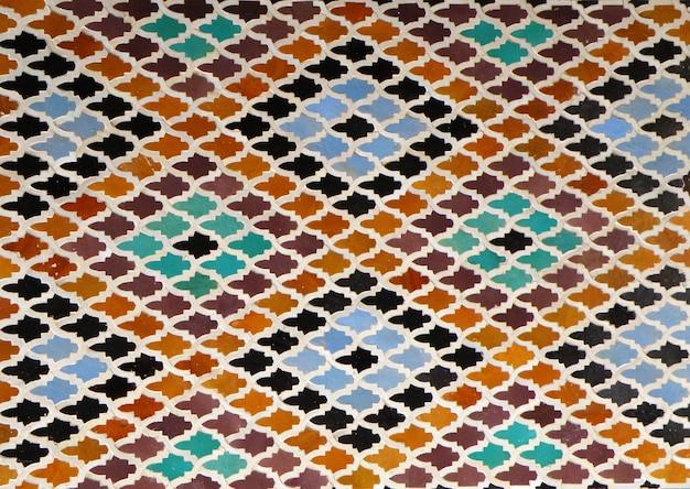 Rautenförmiges muster der marokkanischen art hellblaue orange braune fliesenwand in fez, marokko